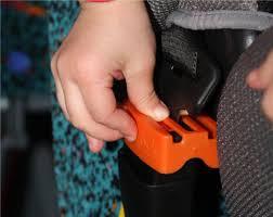 Pouce d'un enfant appuyant sur un cache BELT LOCK évitant le détachement de la ceinture de sécurité pour les enfants