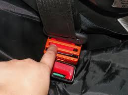 Doigt appuyant sur un cache BELT LOCK évitant le détachement de la ceinture de sécurité pour les enfants